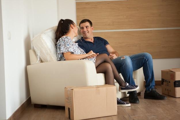 Schöne frau und ehemann ruhen auf ihrem sofa in der neuen wohnung. glückliches paar mit einem süßen moment