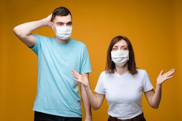 Schöne frau und gutaussehender mann stehen in weißen und blauen t-shirts und weißen medizinischen masken nebeneinander und wollen gesund sein