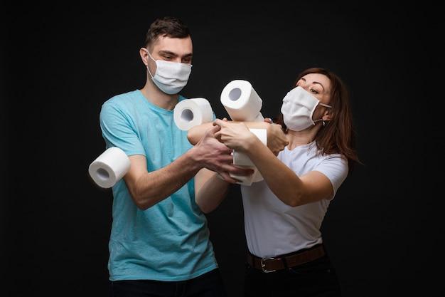 Schöne frau und hübscher mann stehen nebeneinander in weißen und blauen t-shirts und weißen medizinischen masken und kämpfen um viel toilettenpapier
