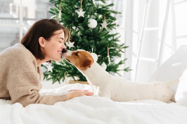 Schöne frau und hund haben süßen kuss, fühlen sich miteinander lieben
