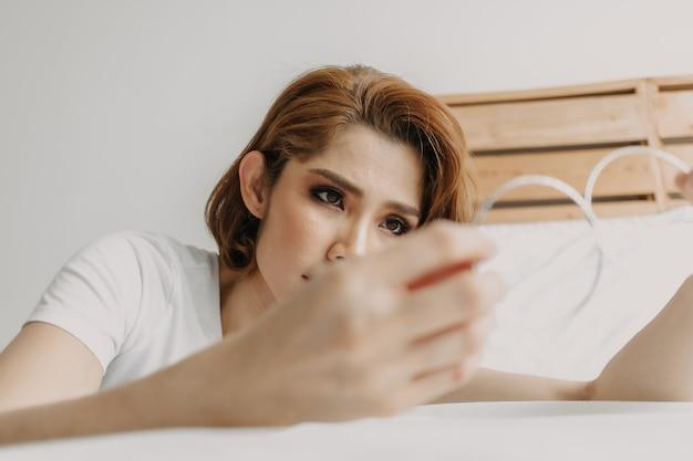Schöne frau und ihre ohrringe in ihrem apartmentzimmer