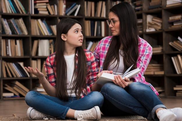 Schöne frau und junges mädchen in der bibliothek