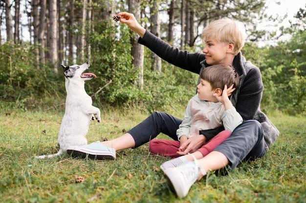 Schöne frau und kleiner junge, die mit hund spielen