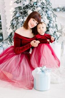 Schöne frau und kleines mädchen, die ähnliche rote kleider tragen, am zimmer mit weihnachtsbaum