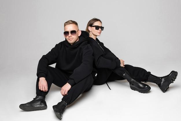 Schöne frau und mann in den schwarzen kleidern, die rücken an rücken sitzen und lächeln. sonnenbrillen auf ihren gesichtern