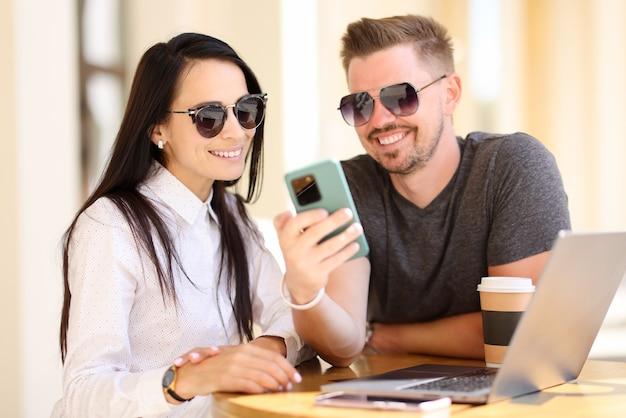 Schöne frau und mann in der sonnenbrille schauen auf telefon und lächeln am runden tisch.
