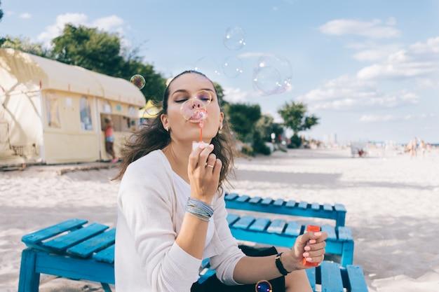 Schöne frau und seifenblasen am strand