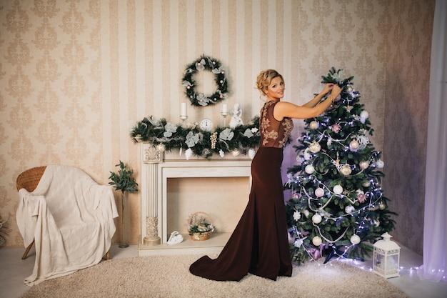 Schöne frau verkleidet einen weihnachtsbaum