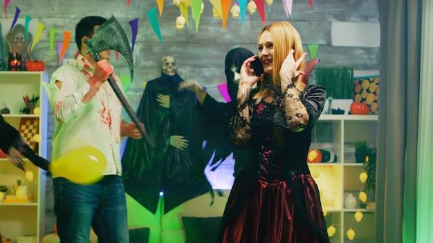Schöne frau verkleidet sich als hexe, die bei halloween-feier in einem raum mit tanzenden menschen mit ihrem telefon spricht