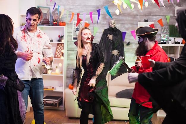 Schöne frau verkleidet wie ein vampir, der mit einem piraten tanzt, während er seine axt bei der halloween-feier hält.