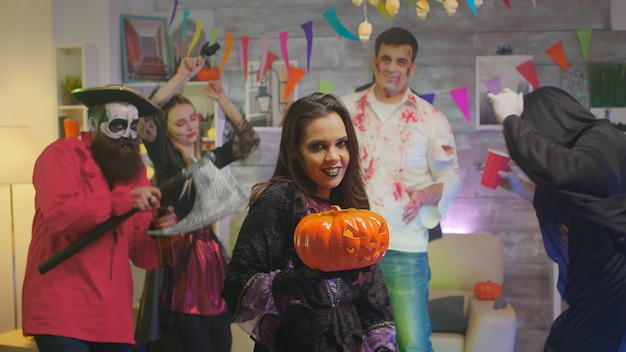 Schöne frau verkleidet wie eine hexe, die zaubersprüche mit einem kürbis auf der halloween-party macht, wo eine gruppe von leuten tanzt und spaß hat.