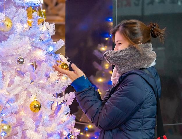Schöne frau verziert und betrachtet weißen weihnachtsbaum für winterfest und feiertagskonzept.