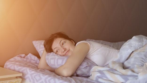 Schöne frau wacht im bett auf, ein gesunder traum, sonnenlicht