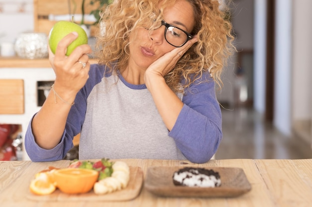 Schöne frau wählt zwischen einem apfel und einer anderen frucht oder einem donut - schwierig, ihren lebensstil zu ändern - 40er jahre mit brille, die einen donut mit einem apfel in der hand sieht