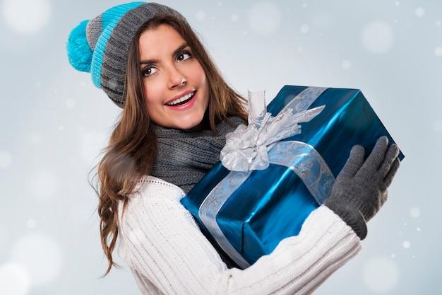 Schöne frau während der magischen weihnachtszeit mit blauem geschenk