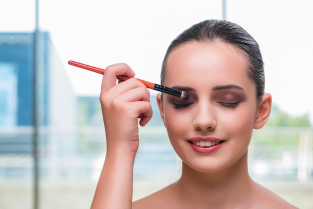 Schöne frau während der make-upkosmetiksitzung