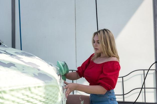 Schöne frau wäscht ihr auto mit grünem schwamm im schaum von schmutzigem