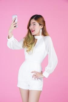 Schöne frau, weißes kleid, welches das telefon und die stimmung des gesichtes zeigt