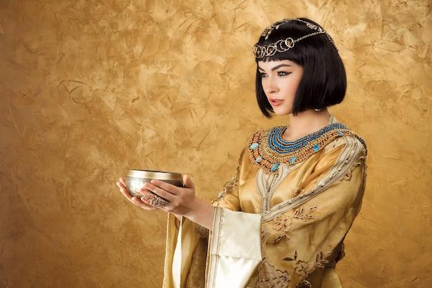 Schöne frau wie ägyptische königin cleopatra mit tasse