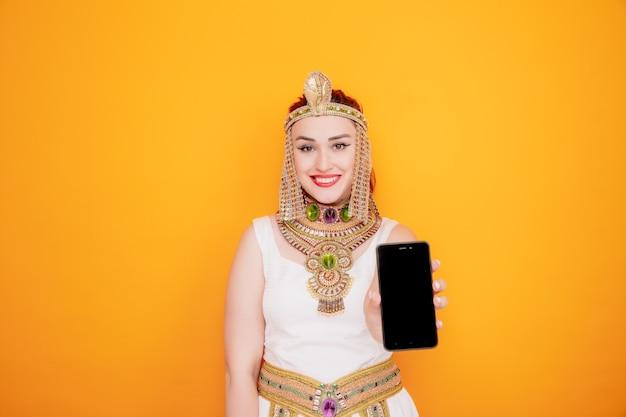 Schöne frau wie kleopatra im alten ägyptischen kostüm, das smartphone glücklich und positiv zeigt, das fröhlich auf orange lächelt