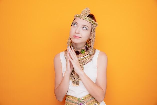 Schöne frau wie kleopatra im alten ägyptischen kostüm, die hände zusammenhält und fasziniert auf orange schaut