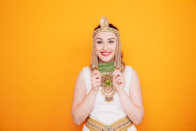 Schöne frau wie kleopatra im alten ägyptischen kostüm, die kreditkarte glücklich und fröhlich hält und breit auf orange lächelt