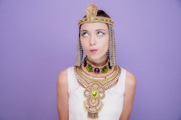 Schöne frau wie kleopatra im alten ägyptischen kostüm, die mit nachdenklichem ausdruck aufschaut, der auf lila denkt