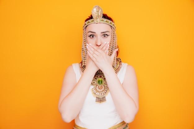 Schöne frau wie kleopatra im alten ägyptischen kostüm, die schockiert ist und den mund mit den händen auf orange bedeckt