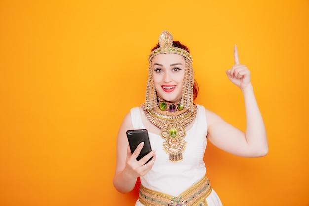 Schöne frau wie kleopatra im alten ägyptischen kostüm, die smartphone mit glücklichem lächeln auf dem gesicht hält, das mit dem zeigefinger zeigt, der eine neue idee auf orange hat
