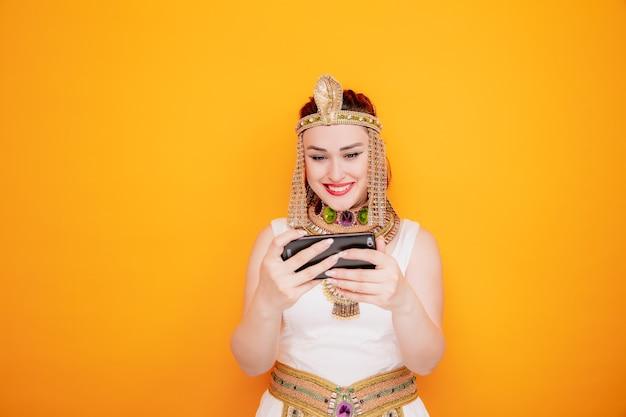 Schöne frau wie kleopatra im alten ägyptischen kostüm, die spiele mit dem smartphone spielt, das glücklich und fröhlich auf orange lächelt
