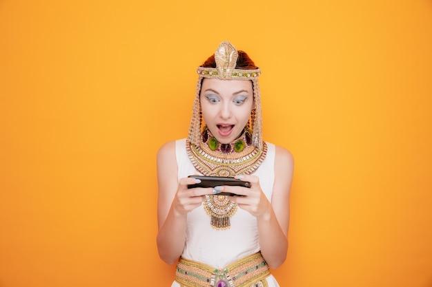 Schöne frau wie kleopatra im alten ägyptischen kostüm, die spiele mit dem smartphone spielt, glücklich und aufgeregt auf orange