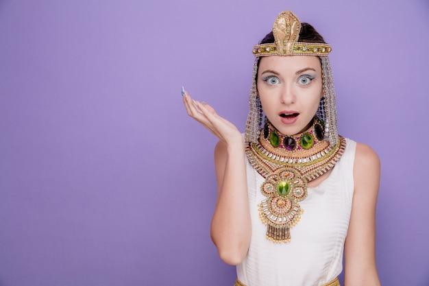 Schöne frau wie kleopatra im alten ägyptischen kostüm erstaunt und überrascht, den arm auf lila zu heben
