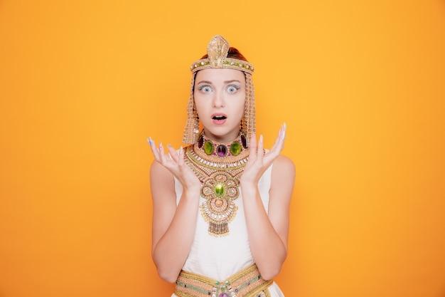 Schöne frau wie kleopatra im alten ägyptischen kostüm erstaunt und überrascht, die arme auf orange zu heben