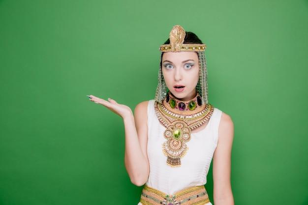 Schöne frau wie kleopatra im alten ägyptischen kostüm erstaunt und überrascht, etwas mit dem arm ihrer hand auf grün zu präsentieren