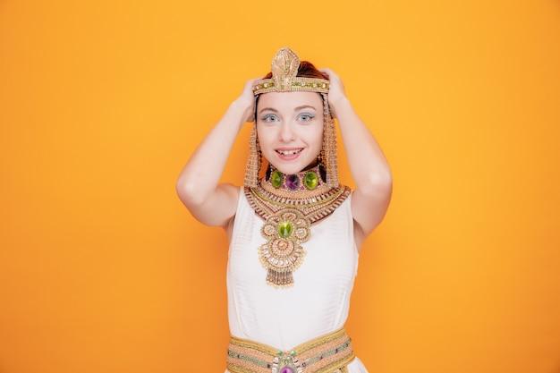 Schöne frau wie kleopatra im alten ägyptischen kostüm glücklich und aufgeregt händchen haltend auf dem kopf auf orange