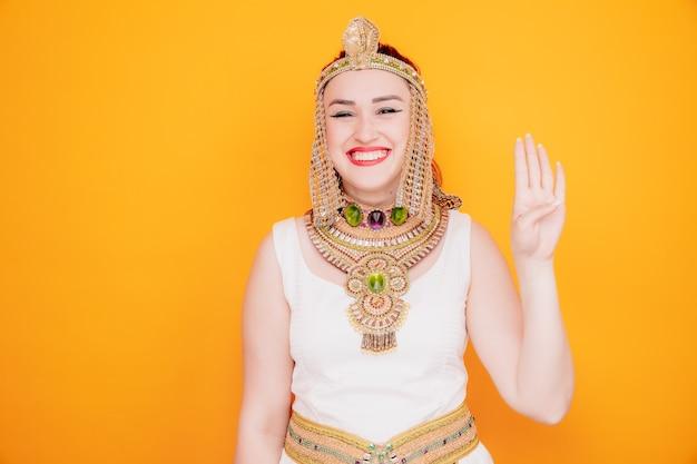 Schöne frau wie kleopatra im alten ägyptischen kostüm glücklich und fröhlich lächelnd, die nummer vier mit den fingern auf orange zeigt