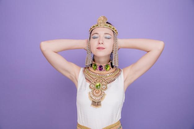 Schöne frau wie kleopatra im alten ägyptischen kostüm glücklich und positiv mit den händen hinter dem kopf mit geschlossenen augen auf lila