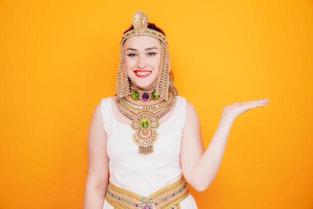 Schöne frau wie kleopatra im alten ägyptischen kostüm mit einem lächeln auf einem glücklichen gesicht, das etwas mit dem arm ihrer hand auf orange präsentiert