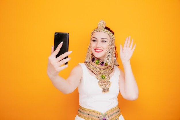 Schöne frau wie kleopatra im alten ägyptischen kostüm mit smartphone mit videoanruf winken mit der hand fröhlich lächelnd auf orange