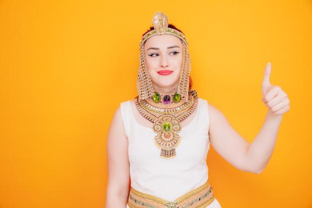 Schöne frau wie kleopatra in altägyptischem kostüm, die beiseite lächelt, zuversichtlich, daumen hoch auf orange zeigend