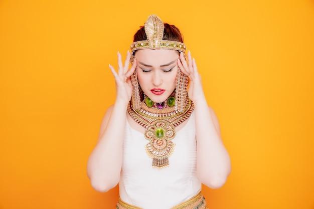 Schöne frau wie kleopatra in altägyptischem kostüm, die genervt und gereizt aussieht und ihre schläfen berührt, die unter kopfschmerzen auf orange leiden