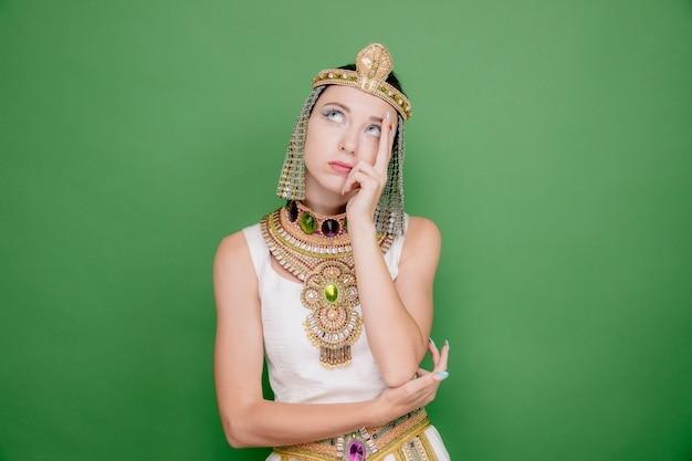 Schöne frau wie kleopatra in altägyptischem kostüm, die mit nachdenklichem ausdruck auf grün aufschaut