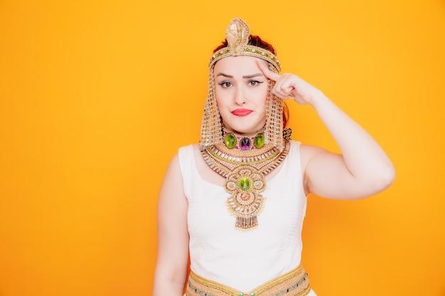 Schöne frau wie kleopatra in altägyptischem kostüm verwirrt, die mit dem zeigefinger auf ihre schläfe zeigt und versucht, sich auf eine aufgabe zu konzentrieren, die hart auf orange ist