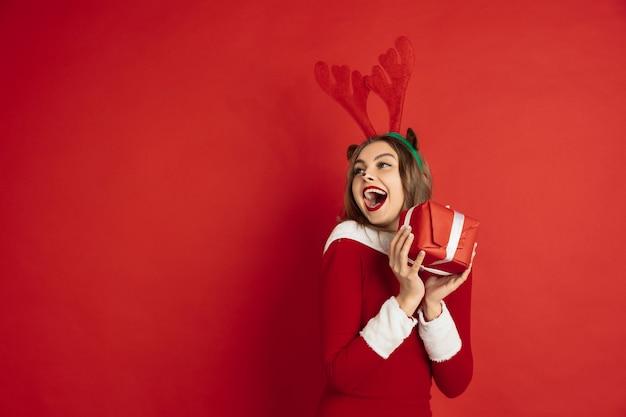 Schöne frau wie weihnachtshirsch isoliert auf roter wand