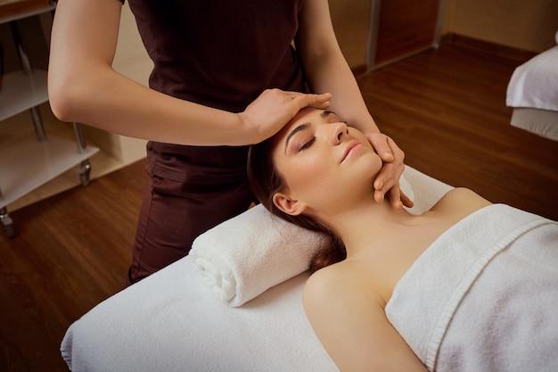 Schöne frau wird eine gesichtsmassage im spa-salon gegeben