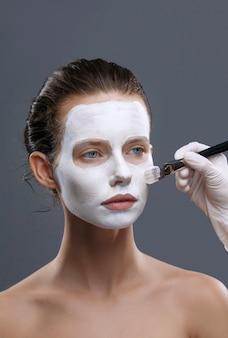 Schöne frau wird eine weiße kosmetische maske aus schwarzen punkten isoliert angewendet