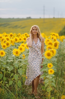 Schöne frau wirft im landwirtschaftlichen feld mit sonnenblume an einem sonnigen sommertag auf