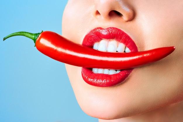 Schöne frau zähne essen red hot chili pfeffer zahnklinik patient. bild symbolisiert mundpflege zahnmedizin, stomatologie.