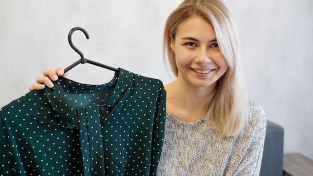Schöne frau zeigt ein kleid auf einem kleiderbügel. sie spricht über mode und nimmt einen videoblog auf
