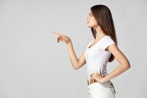 Schöne frau zeigt ihren daumen zur seite seitenansicht weißes t-shirt